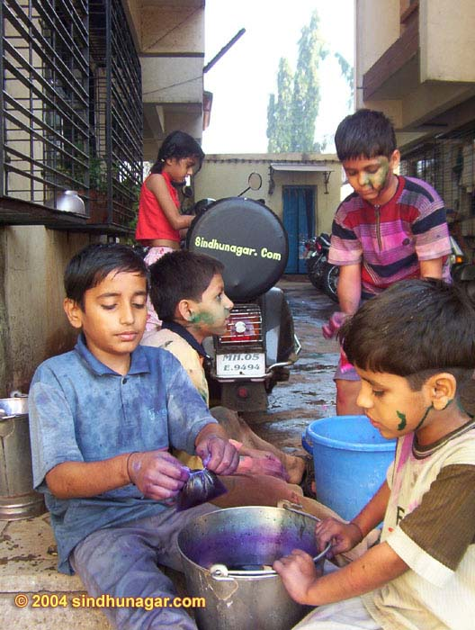 Kids preparing colored water and baloons early morning on Holi