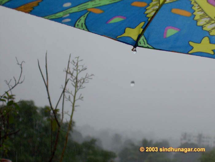 Last few days of monsoon. Sky is turned dark in the day time visible from umbrella.
